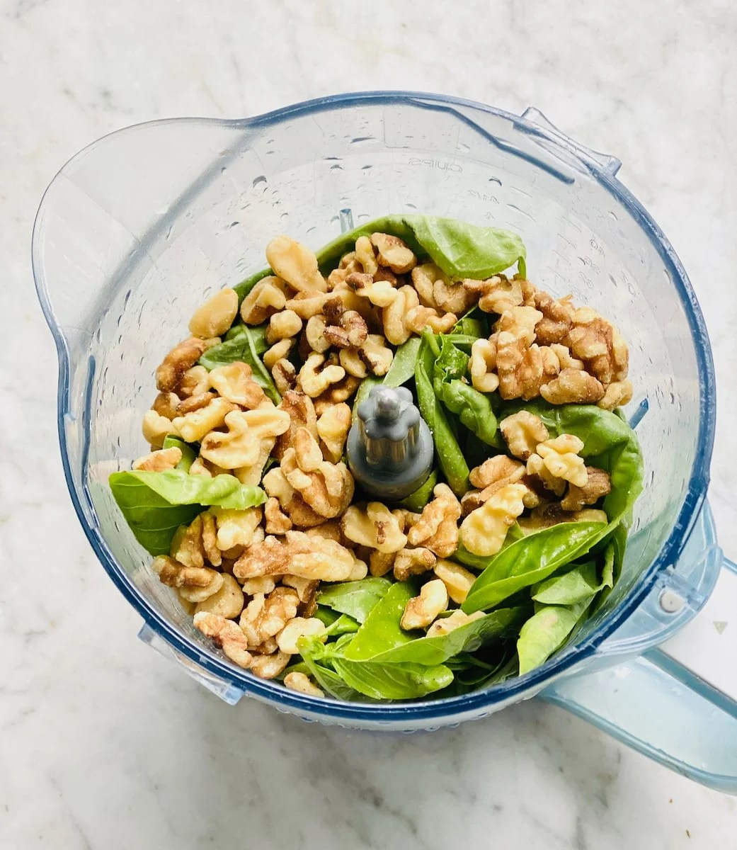 fresh basil and walnuts in a blender before processing