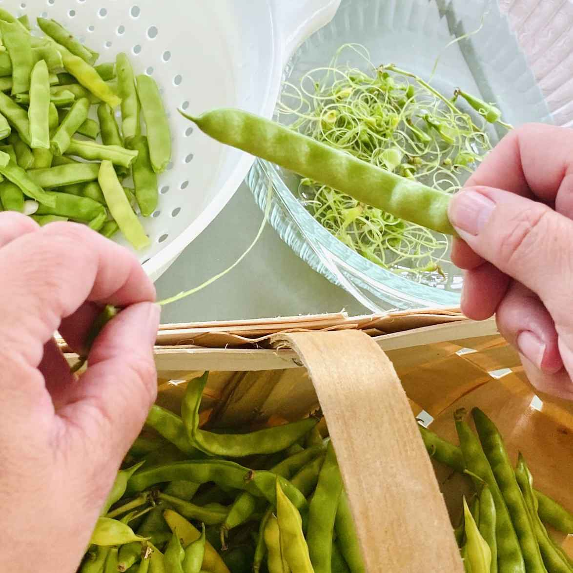 two hands showing how to string a green bean