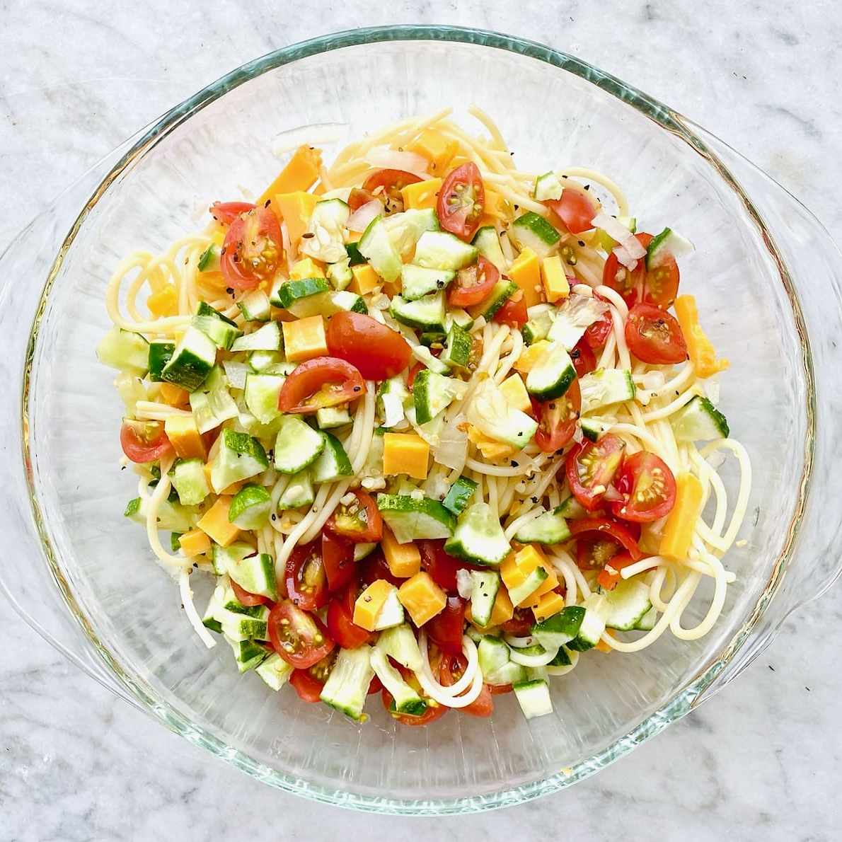 fresh tomatoes, cucumbers, onions and olives on top of spaghetti pasta in a clear bowl