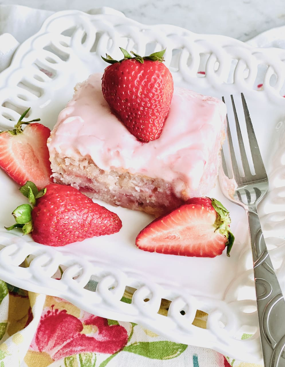 slice of strawberry cake on a white plate surrounded by strawberries