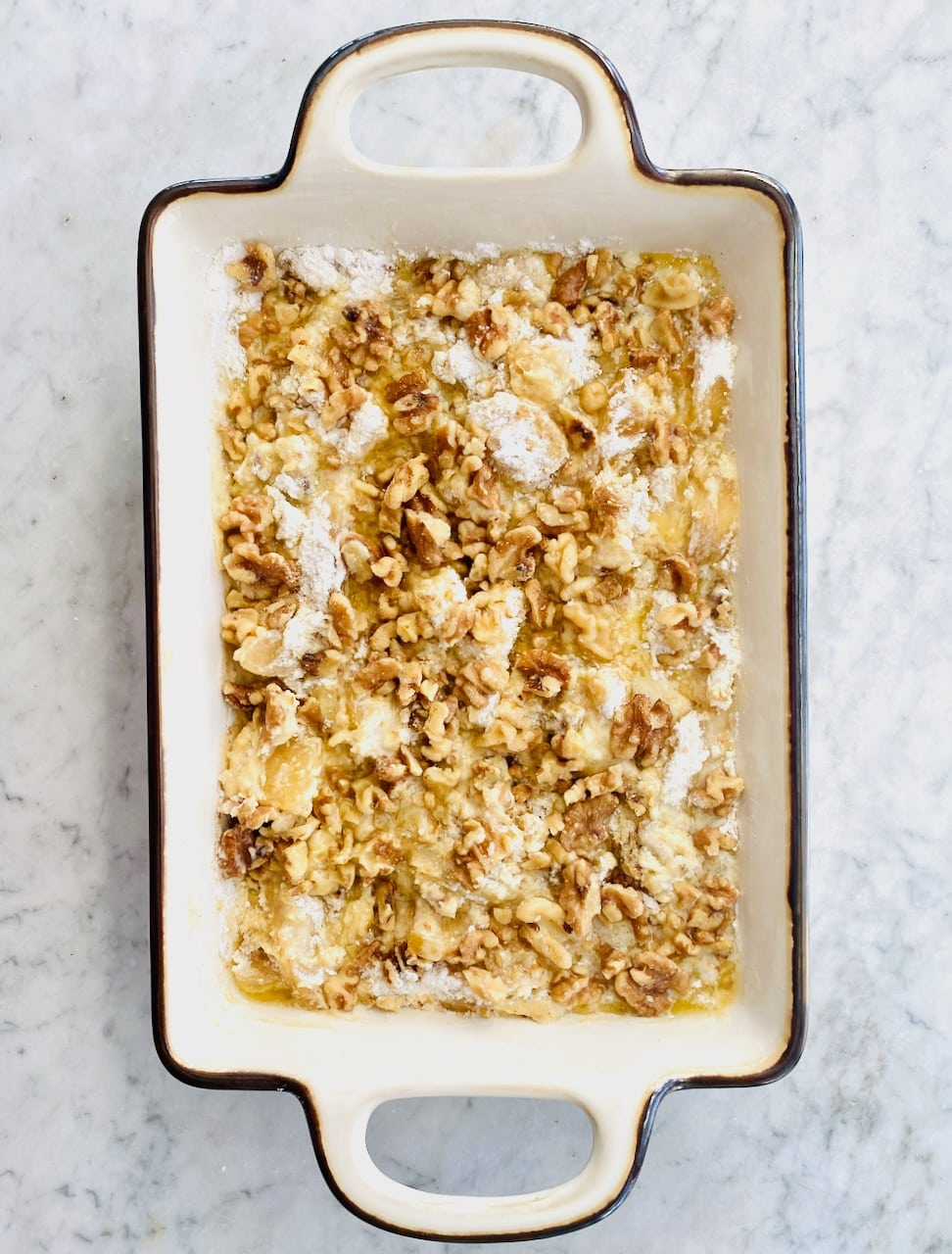 dump cake in a rectangular dish with butter, cake mix and walnuts on top.