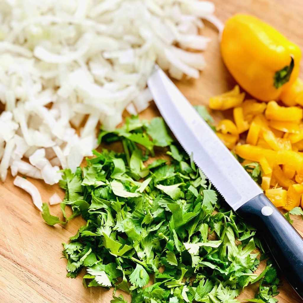 cilantro, onions and yellow peppers diced on a cutting board