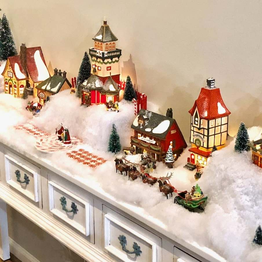 christmas snow village on a white table.