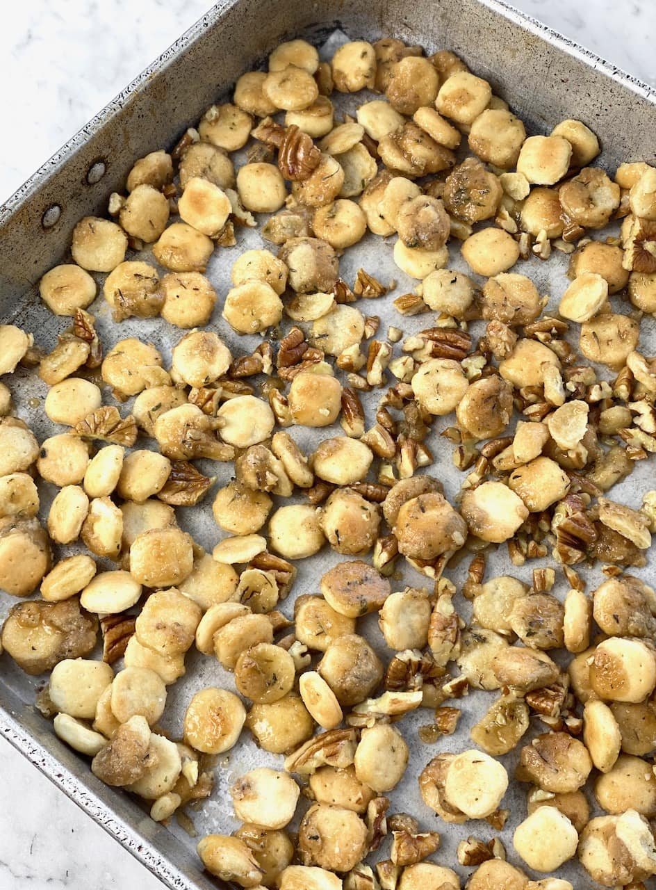 sheet pan with oyster crackers and pecans after coming out of the oven.