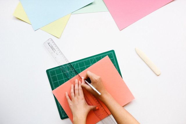 Someone using the Pomodoro Technique to focus on their creative work: using a ruler and construction paper to make a design.