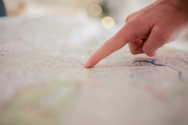 An index finger pointing to a map.