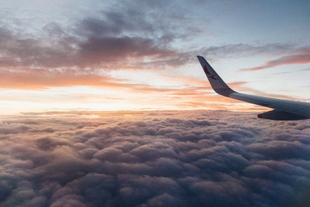 The left wing of an airplane as it soars through the sky, over thick clouds at sunset.