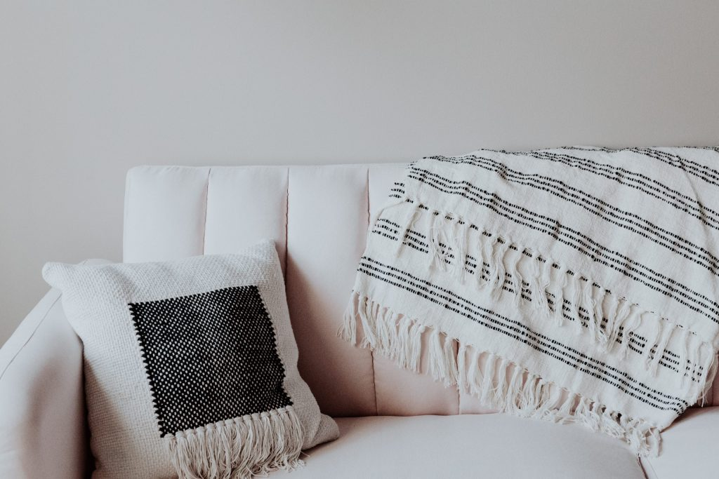 A white couch with a white pillow and blanket.
