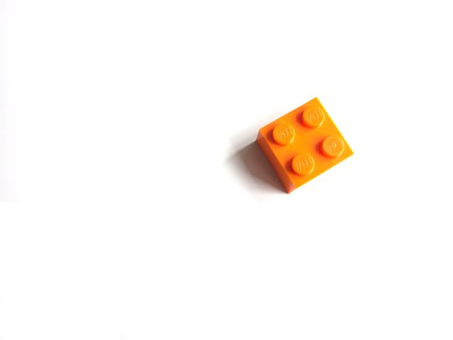 One orange building block on a white background.