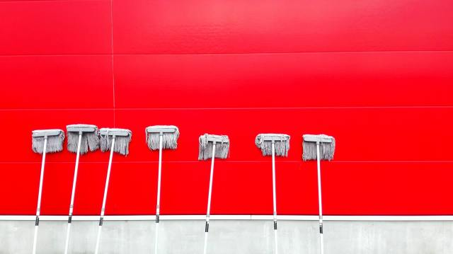 Mops cleaning a bright red wall.
