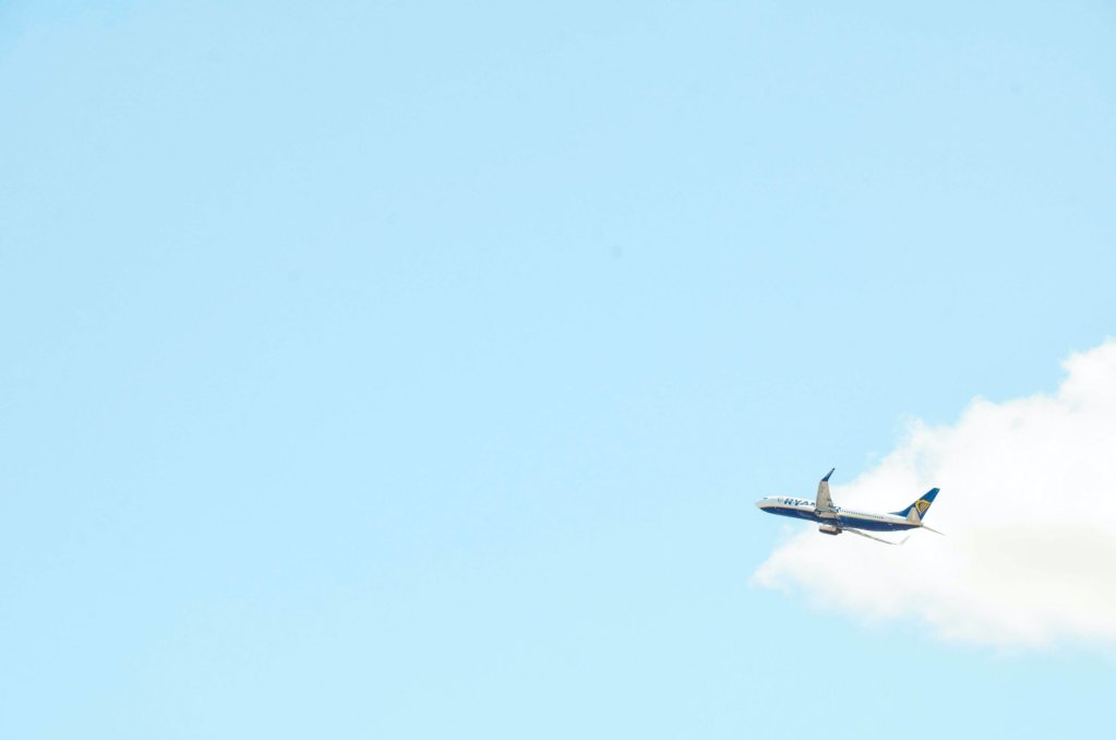 A plane in the baby blue sky.