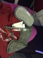 Amenities kit: eye mask, earplugs, lotion, lip balm, toothbrush and paste, and socks