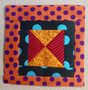 Multi-colored quilt block of vivid colors: red, orange, black, teal, and purple.