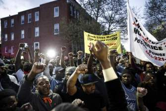 BALTIMORE, MD - ARPIL 21:  Protestors participate in a vigil for Freddie Gray down the street from the Baltimore Police Department's Western District police station, April 21, 2015 in Baltimore, Maryland.  Gray, 25, died from spinal injuries on April 19, one week after being taken into police custody. (Photo by Drew Angerer/Getty Images)