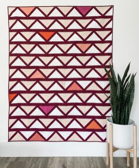Purple, peach, and orange fabric Cafe Tiles Quilt hanging on a wall with a plant in front of it