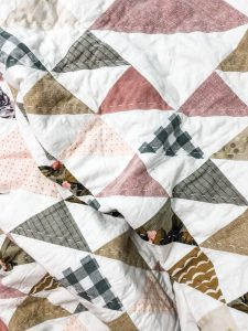 A quilt made of Half Square triangles in earth tones and florals, all hand quilted