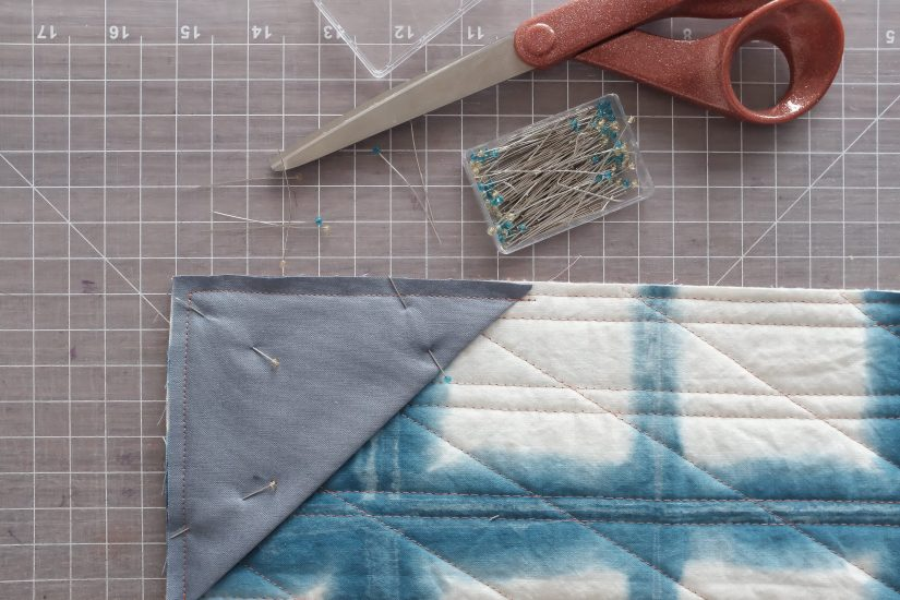 the corner of a the back of a quilt with a folded square pinned to it, to prepare to hang on a wall.