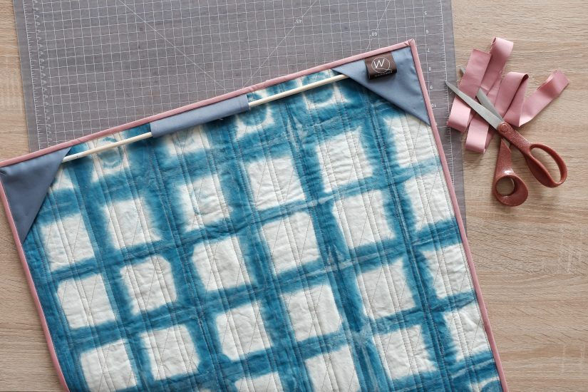 Back of quilt with fabric holding a wooden stick so quilt can hang on a wall.