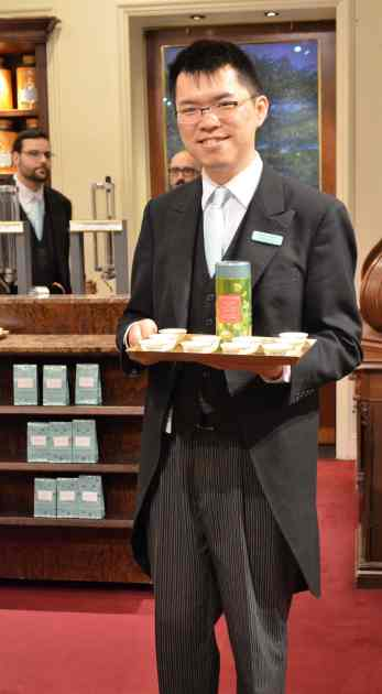 Offering tea samples in a frock coat.