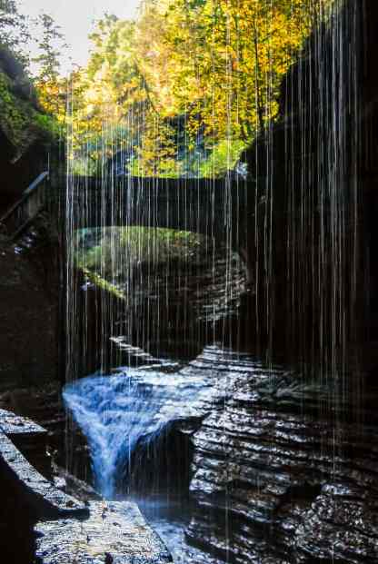 walking behind a waterfall at Watkins Glen Gorge Trail