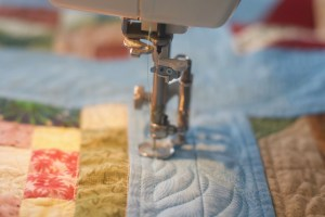 Close-up photo of a quilt and a free-motion quilting foot