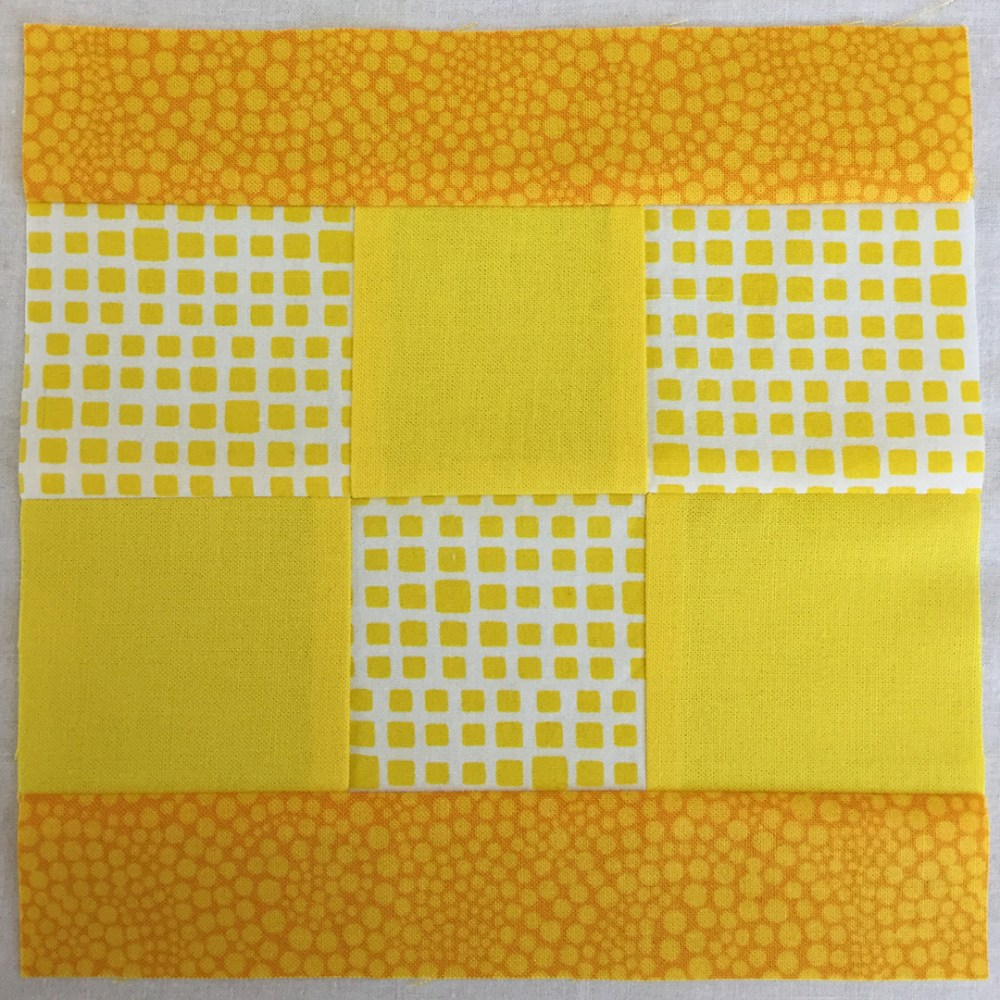a quilt block in yellow