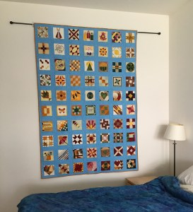 A completed quilt hanging on a wall from a rod mounting
