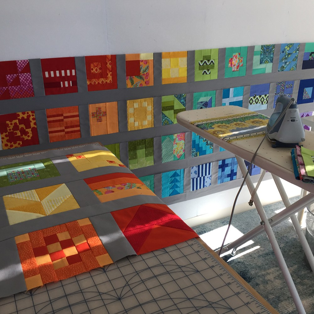 detail of a sewing space with rows on the design wall and draped over a cutting table