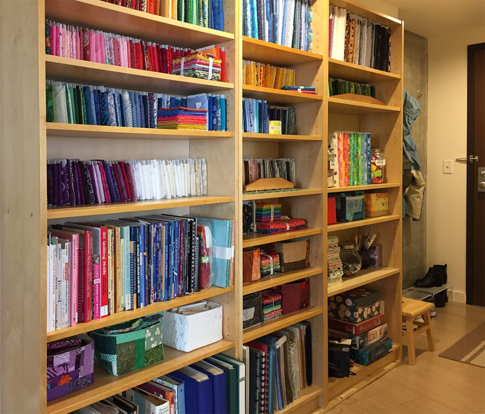 Bookshelves filled with fabric, books, and supplies