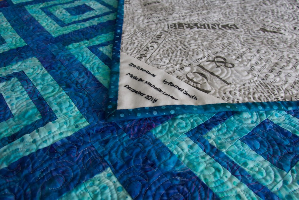 blue and turquoise quilt with diamond pattern