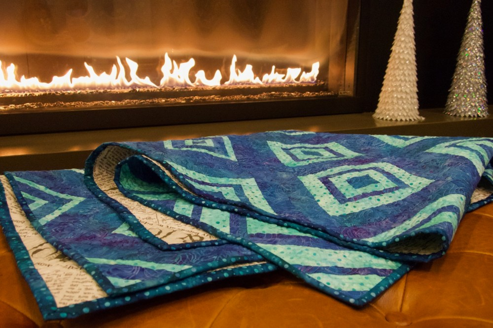blue and turquoise quilt with diamond pattern in front of a fireplace