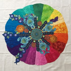 a rainbow-colored circle with fussy-cut fabric pieces on top