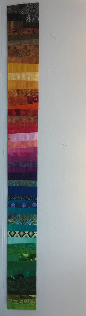 a long, narrow strip of fabric made up of pieces of rainbow-colored fabric