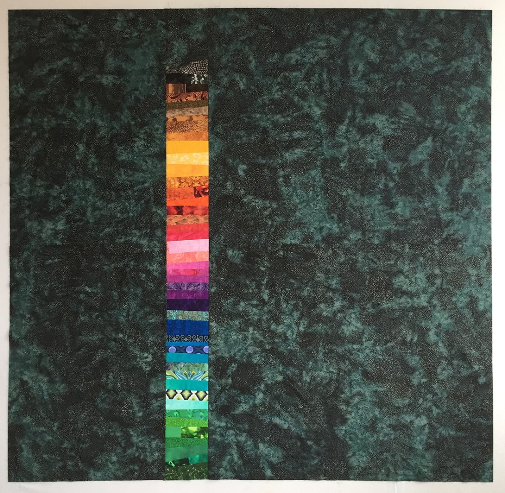 a rainbow stripe of fabric set into a teal background