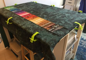 quilt back clamped to a table, wrong side up