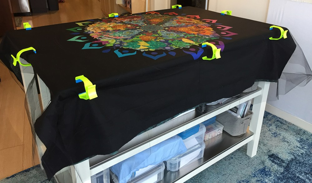 black tulle clamped to a table over the quilt top, batting, and backing