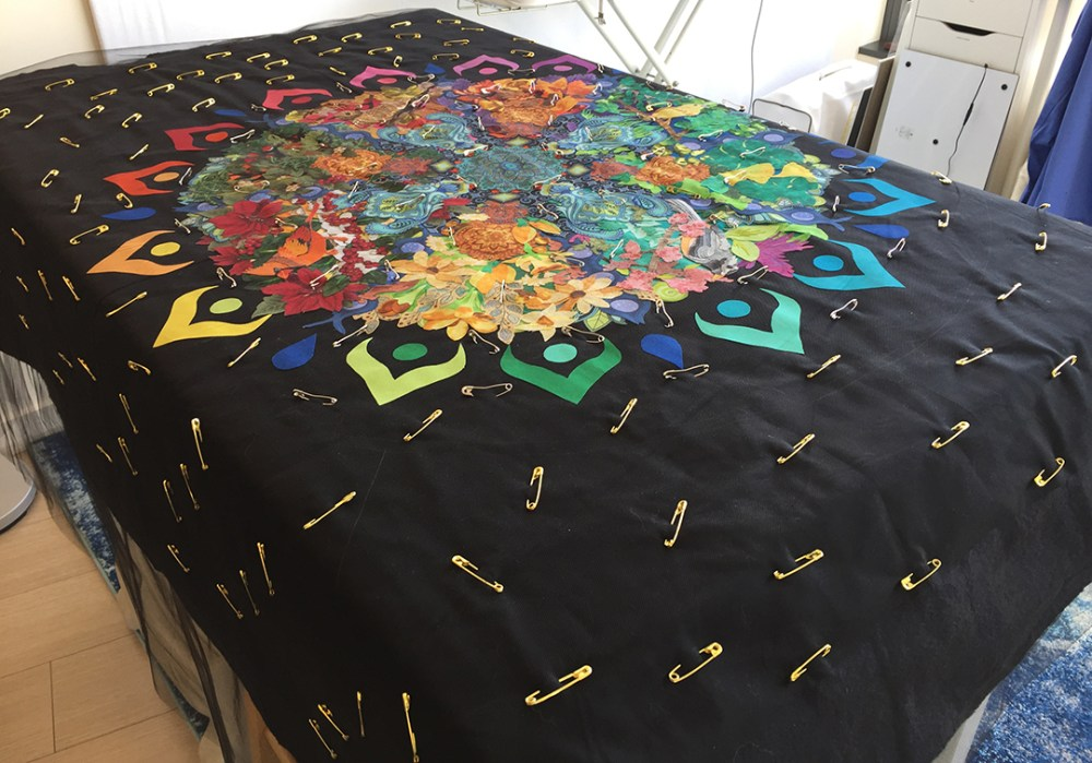 the pin-basted quilt draped over a table
