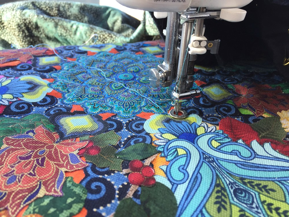 close up of a sewing machine needle in a quilt top with some quilting completed