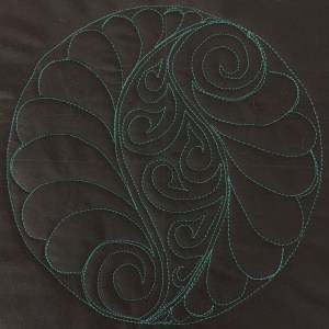 """a practice block with blue thread on black fabric showing a feathery """"S"""" shape"""