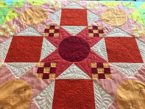 a close up of the center of the quilt showing different quilting designs