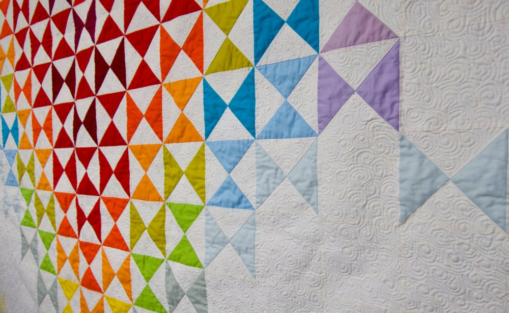 detail of quilt showing colored squares and quilting