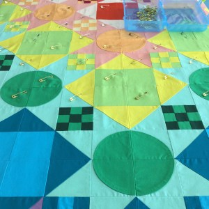 a close up of a quilt top that has been partly pin basted