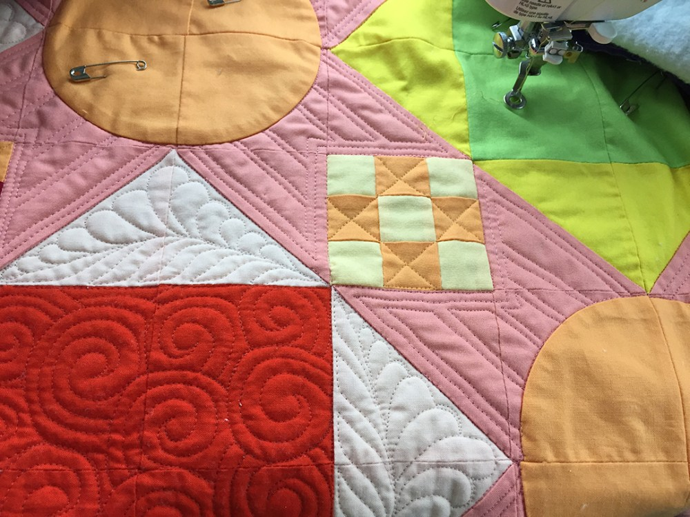 a close up of quilting showing swirls, feathers, and lines