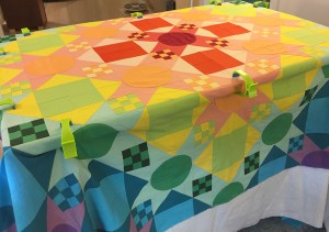a colorful quilt layered with the backing and batting and clamped to a table for basting