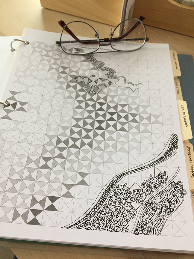 sketching quilt designs on a printout of the quilt top