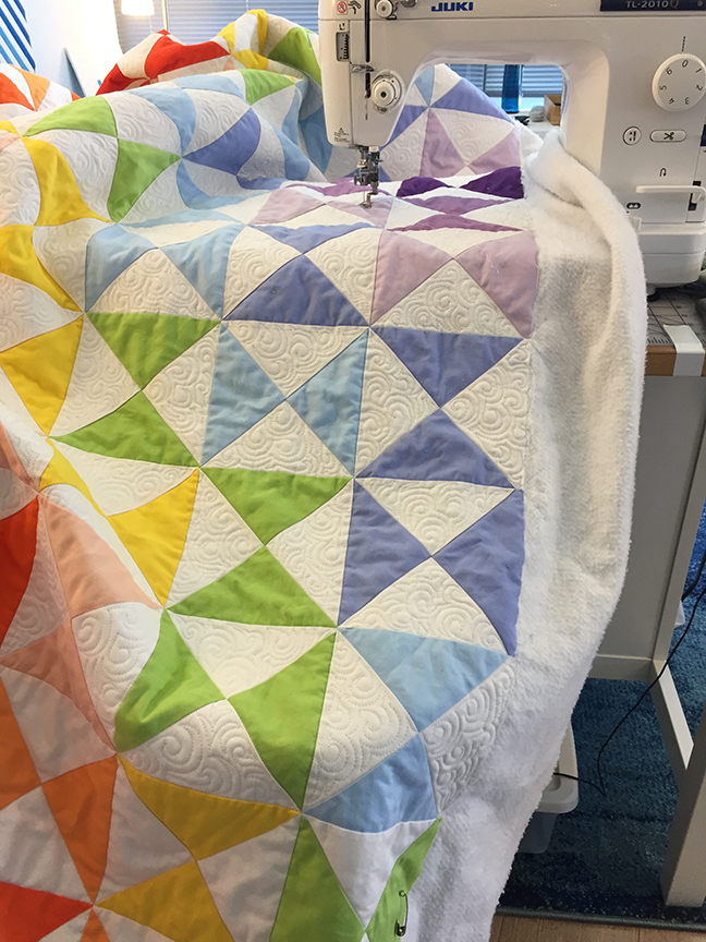 large quilt loaded into a sit-down machine