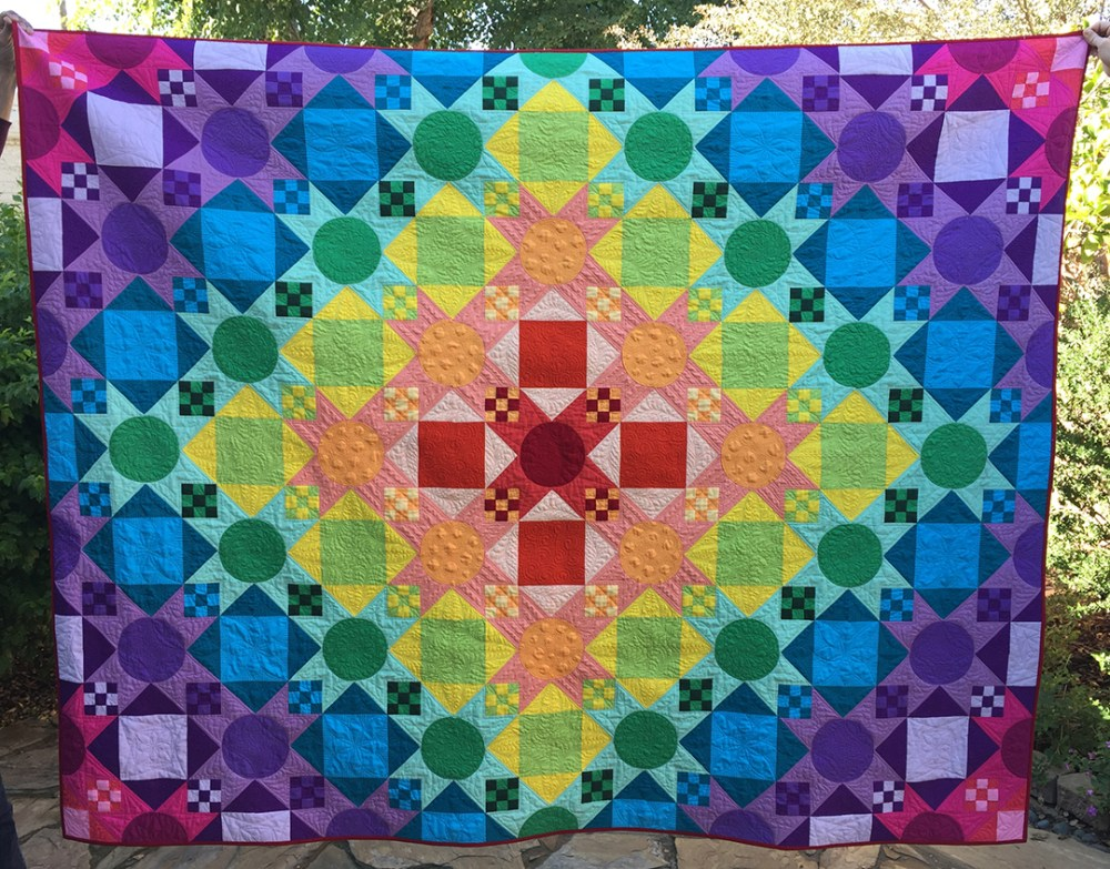 a colorful quilt being held up by two people