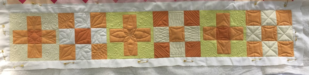 A row of quilted blocks in shades of yellow and orange