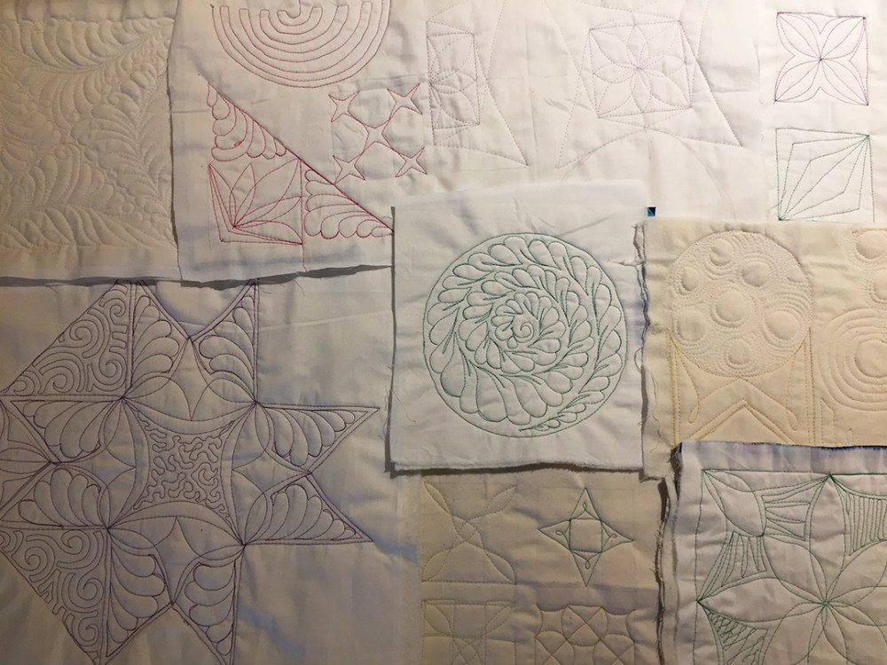several practice quilt sandwiches with different quilting designs