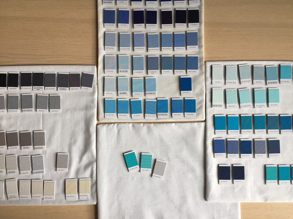 fabric-covered magnetic swatch boards with gray and blue swatches on them